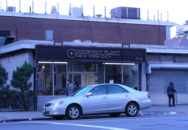 car parked in front of low red building with store sign reading 'The Doughnut Plant'