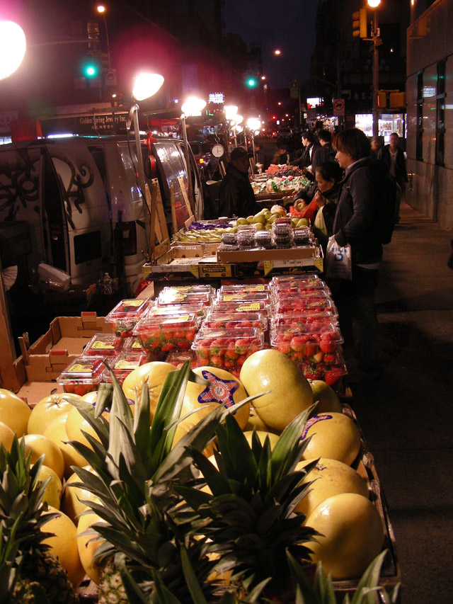 fruit stand on sidewalk with lights on at night