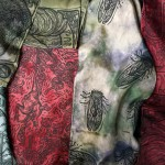 hand-dyed (reds and greens) and block-printed silk scarves feature images of plucked and hanging chickens, cicadas, decorative chickens