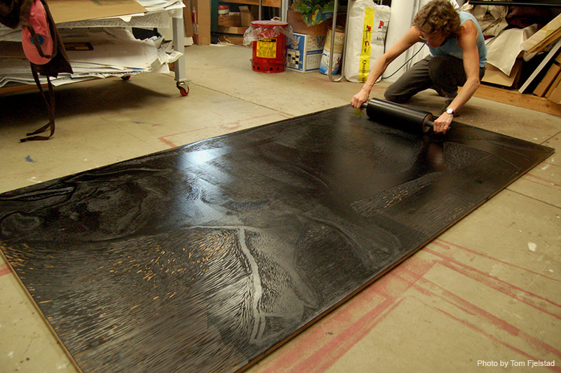 Medaris inks up the 8ft hog block on the floor with black ink and a large 2-handled roller