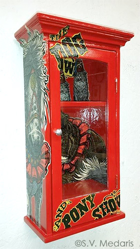 red shiny cabinet decoupaged with pieces of Dog & Pony Show woodcut broadside by S.V. Medaris