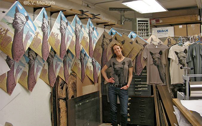 Artist, S.V. Medaris in brown alpaca tee, smiles in front of lines of prints: full-color Alpaca Sky prints and alpaca t-shirts, all drying.