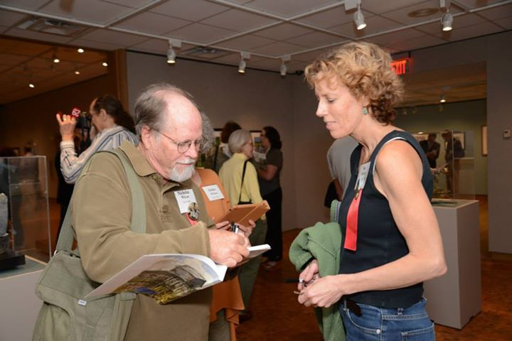 artists sign each others' books at Birds of Art Opening weekend. S.V. Medaris looks on at artist signs her book.