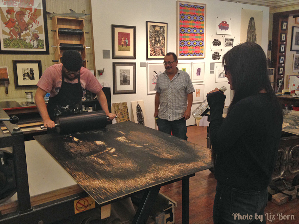 man inks 5ft woodblock while man and woman look on. framed artwork on walls